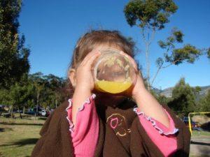 Niña tomando jugo de naranja